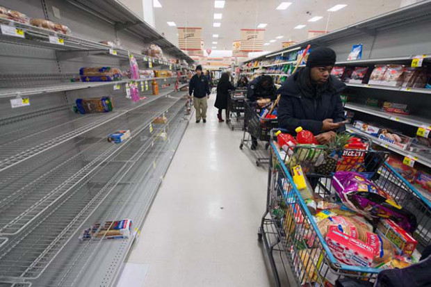 A long line of shoppers wait beside mostly-empty shelves in the bread aisle of a grocery store, as people stocked up on items ahead of an approaching snowstorm, in Alexandria, Virginia, USA, 12 February 2014.