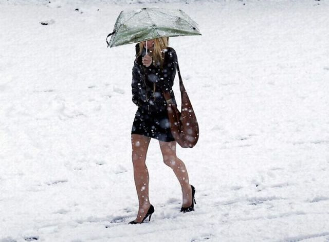winter-wonderland-dressing-for-the-cold-a-woman-with-high-heels-walking-through-the-snow