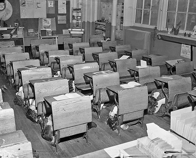 "Original Caption: Open books are left on desks of the children of class 42-Junior High Elementary, as they dive under their desks during an ""A"" bomb drill.  Top view of children under their desks."