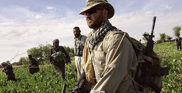 LASHKAR GAH, AFGHANISTAN - APRIL 03:  An American supervisor from the DynCorp security contractor watches Afghan forces cut opium poppies on April 3, 2006 near Lashkar Gah in the Helmand province of southern Afghanistan. Afghan forces are feverishly working to eradicate the poppy fields before the harvest begins in the next month. The Taliban reaps huge profits from protecting the opium trade, according to Afghan officials. Afghanistan produces up to 85 percent of the world's opium and Helmand province almost half of that.  (Photo by John Moore/Getty Images)