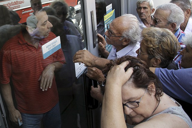 Pensioners waiting outside a closed National Bank branch and hoping to get their pensions, argue with a bank employee (L) in Iraklio on the island of Crete, Greece June 29, 2015. Greeks struggled to adjust to shuttered banks, closed cash machines and a climate of rumours and conspiracy theories on Monday as a breakdown in talks between Athens and its creditors plunged the country deep into crisis.    REUTERS/Stefanos Rapanis   - RTX1I94A