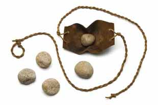 Sling and five smooth stones used by David to kill Goliath on a white background